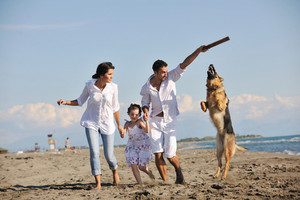 Happy Family Playing With Dog Sur la plage