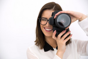 Happy female photographer with camera over gray background