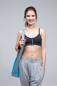 Happy fit woman standing with yoga mat over gray background