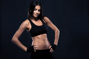 Happy fitness woman with perfect body posing over black background and looking at camera