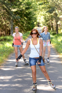 Happy girl friends skating outdoors on countryside road summer sport