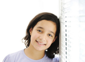 Happy girl indoor, leaning on the window