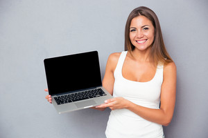 Happy girl showing blank laptop screen