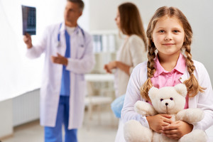 Happy girl with teddy bear looking at camera on background of doctor showing x-ray results to her mother