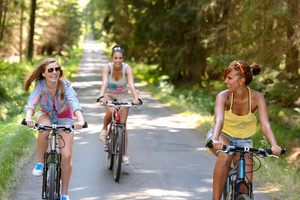 Happy girls riding bicycles outside enjoy summer sport