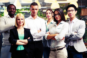 Happy group of co-workers with arms folded standing in office