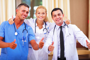 Happy group of doctors showing thumbs up
