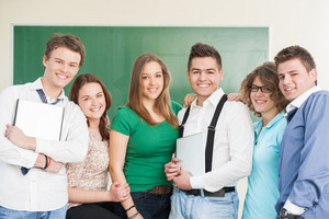Happy group of students smiling on a blackboard