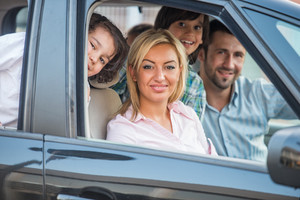 Happy joyful smiling family looking through car window