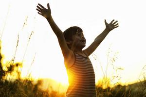 Happy kid enjoying in nature at sunset