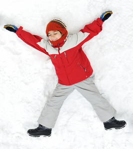 Happy kid lies on snow ground