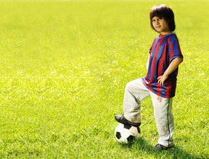 happy kid playing football in a park outdoors