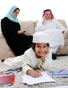 Happy kid working on homework at home with his family