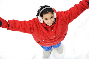 Happy little girl standing on snow ground