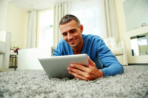 Happy lying on the carpet and using tablet computer at home