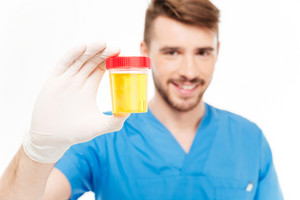 Happy male doctor holding bottle of urine sample isolated on white background. Focus on bottle