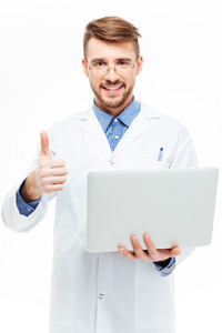 Happy male doctor holding laptop computer and showing thumb up isolated on a white background