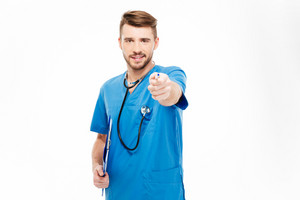 Happy male doctor pointing pen at camera isolated on a white background