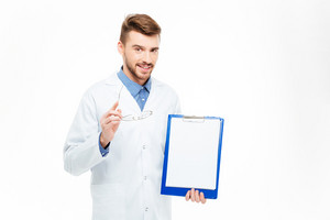 Happy male doctor showing blank clipboard isolated on a white background
