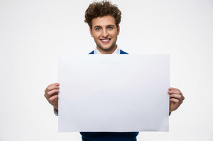 Happy man holding empty paper and looking at camera