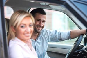 Happy man in a car driving a beautiful happy woman