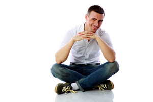 Happy man sitting at the floor over white background