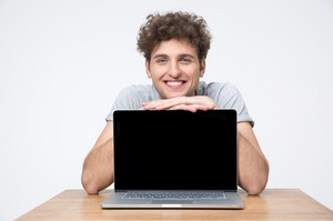 Happy man sitting at the table and showing laptop screen