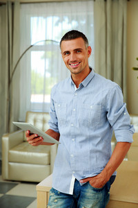 Happy man standing with tablet computer at home