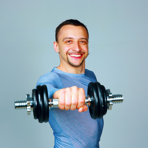 Happy man working out with dumbbells over gray background