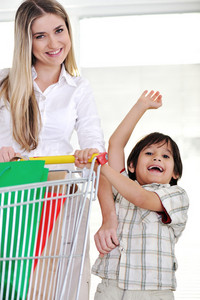 Happy mother with her kid shopping using basket