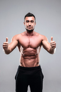 Happy muscular man with thumbs up over gray background