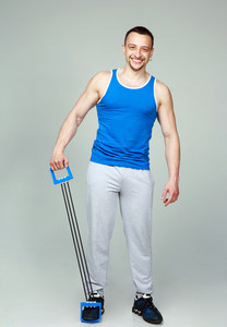 Happy muscular sportsman with expanders on gray background