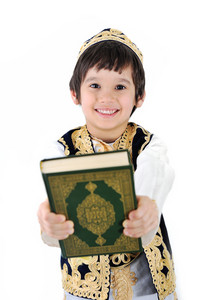 Happy muslim kid holding holy Quran