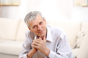 Happy relaxed elderly  man on sofa
