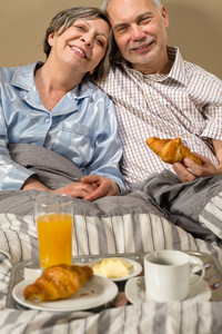 Happy retired couple eating croissant for breakfast in bed