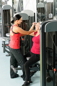 Happy senior woman at gym workout with personal trainer assistance