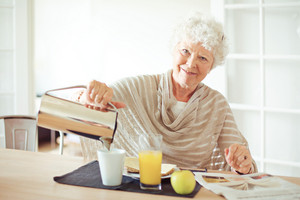 Happy senior woman having her breakfast at home looking at you