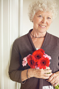 Happy senior woman holding a bouquet of fresh flowers