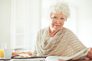 Happy senior woman reading her morning newspaper