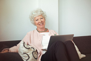 Happy senior woman sitting on the couch at home with laptop