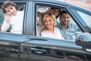 Happy smiling family posing in car
