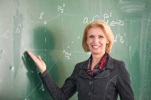 Happy smiling female teacher showing chalkboard