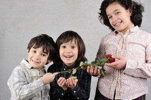 Happy smiling kids with red rose