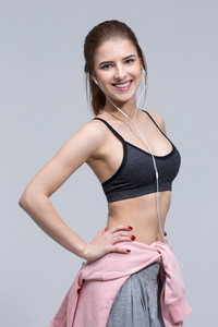 Happy smiling sports woman standing over gray background