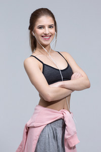 Happy smiling sports woman standing with arms folded over gray background
