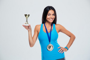Happy sports woman holding winner cup over gray background. Looking at camera