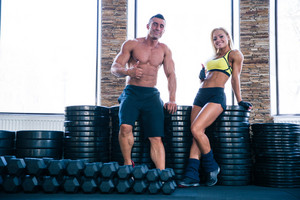 Happy sporty woman and muscular man showing thumb up in gym