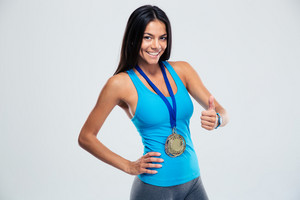 Happy sporty woman showing thumb up sign over gray background. Looking at camera