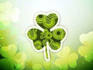 Happy St. Patrick's Day Concept With Beautiful Floral Decorated Clover Leaf On Shiny Green Background.