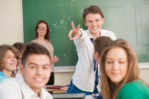 Happy student holding up two fingers in a classroom